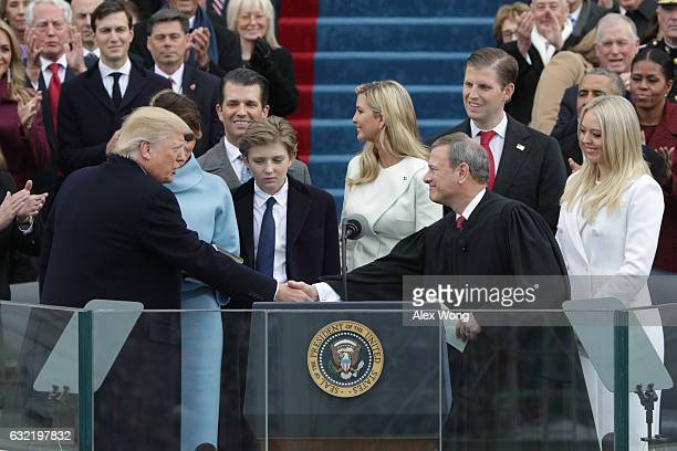 President Donald Trump shakes hands with Supreme Court Chief Justice John Roberts as his family looks on on the West Front of the US Capitol on...