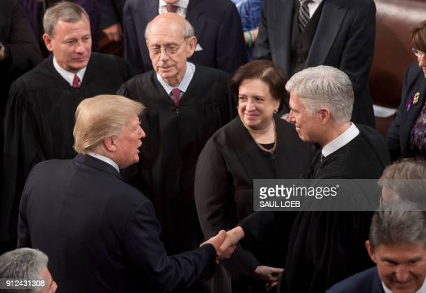US President Donald Trump shakes hands with Supreme Court Justice Neil Gorsuch alongside US Supreme Court Chief Justice John Roberts Justice Stephen...
