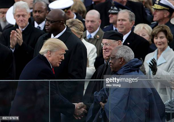President Donald Trump shakes hands with Supreme Court Justice Clarence Thomas on the West Front of the U.S. Capitol on January 20, 2017 in...