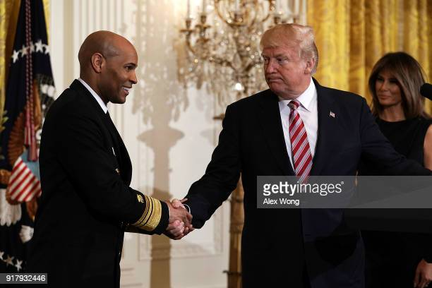 S President Donald Trump shakes hands with Surgeon General Jerome Adams as first lady Melania Trump looks on during a reception in the East Room of...
