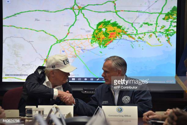 President Donald Trump shakes hands with Texas Governor Greg Abbott at the Texas Department of Public Safety Emergency Operations Center in Austin...