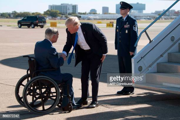 US President Donald Trump shakes hands with Texas Governor Greg Abbott as he arrives at Dallas Love Field in Dallas Texas on October 25 2017 to...