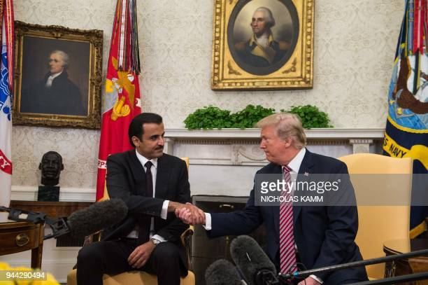 US President Donald Trump shakes hands with the Emir of Qatar Sheikh Tamim bin Hamad alThani in the Oval Office at the White House in Washington DC...