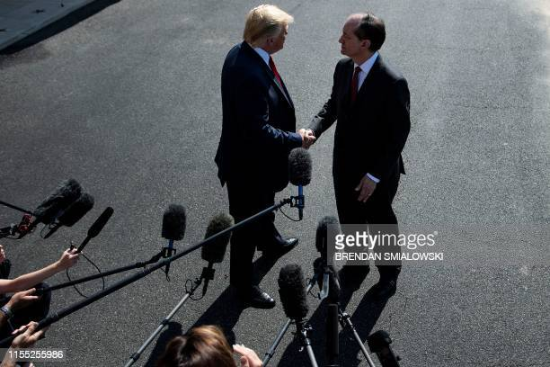 US President Donald Trump shakes hands with US Labor Secretary Alexander Acosta during a media address early July 12 2019 at the White House in...