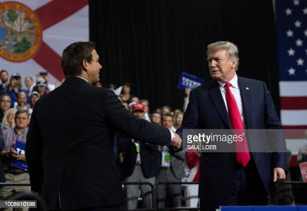 US President Donald Trump shakes hands with US Representative Ron DeSantis Republican of Florida and candidate for Florida Governor as he speaks...
