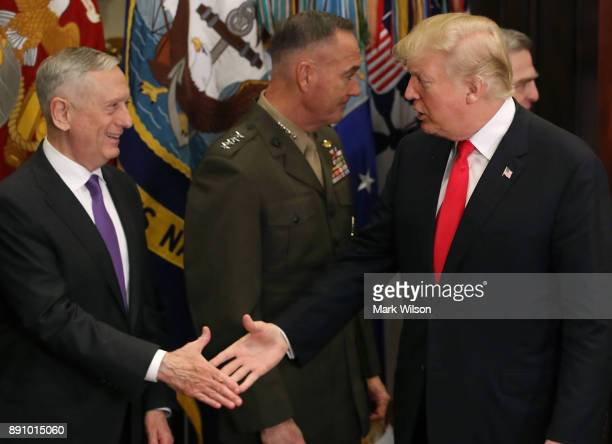 S President Donald Trump shakes hands with US Secretary of Defense James Mattis before signing the HR 2810 National Defense Authorization Act for...