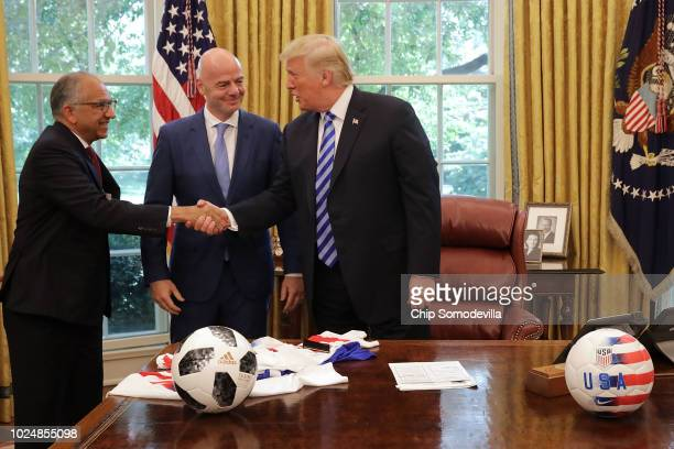 S President Donald Trump shakes hands with US Soccer President Carlos Cordeiro and FIFA President Gianni Infantino in the Oval Office at the White...