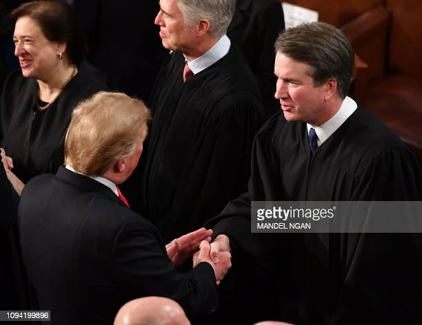 President Donald Trump shakes hands with US Supreme Court Justice Brett Kavanaugh before delivering the State of the Union address at the US Capitol...