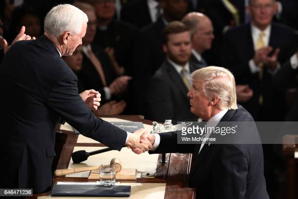 S President Donald Trump shakes hands with Vice President Mike Pence after Trump addressed a joint session of the US Congress February 28 2017 in the...