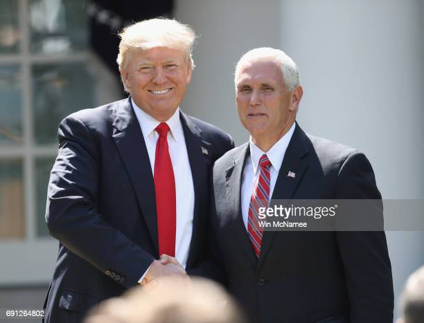 S President Donald Trump shakes hands with Vice President Mike Pence prior to announcing his decision regarding the United States' participation in...