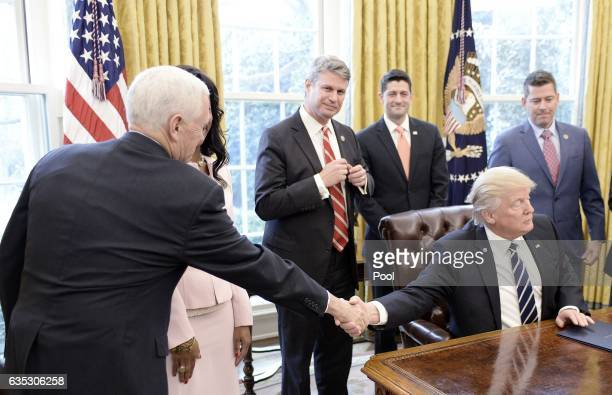 US President Donald Trump shakes hands with VicePresident Mike Pence after signing HJ Res 41 in the Oval Office of the White House on February 14...