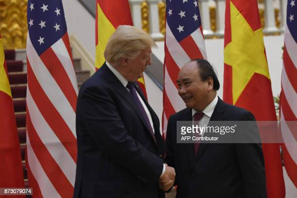 President Donald Trump shakes hands with Vietnamese Prime Minister Nguyen Xuan Phuc in Hanoi on November 12, 2017. Trump arrived in the Vietnamese...