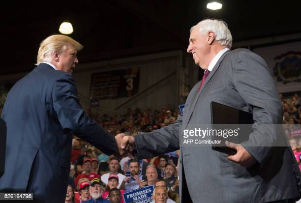 President Donald Trump shakes hands with West Virginia Governor Jim Justice, who announced during the rally he would switch parties from Democrat to...