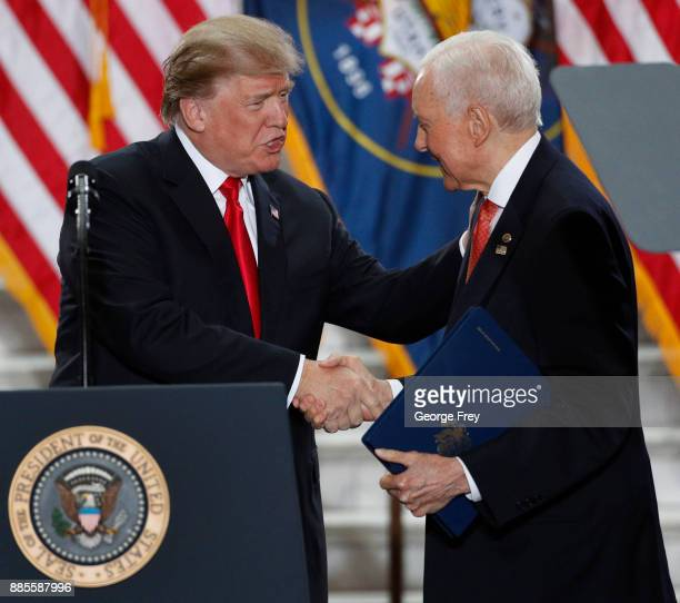 S President Donald Trump shakes the hand of Senator Orrin Hatch as he arrives for a speech at the Rotunda of the Utah State Capitol on December 4...