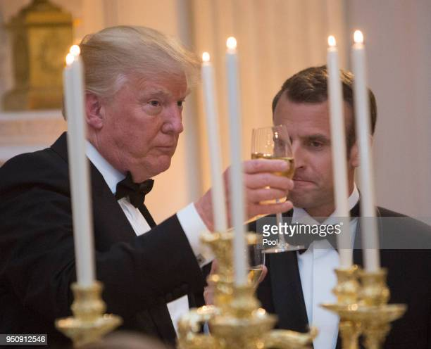 S President Donald Trump shares a toast with French President Emmanuel Macron during the State Dinner for Macron and French first lady Brigitte...