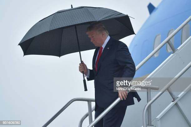 President Donald Trump shelters from the rain under an umbrella as he disembarks from Airforce One in Los Angeles, California on March 13, 2018.