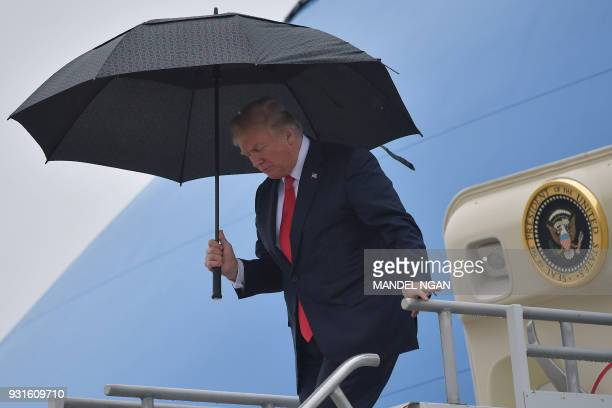 US President Donald Trump shelters from the rain under an umbrella as he disembarks from Airforce One in Los Angeles California on March 13 2018