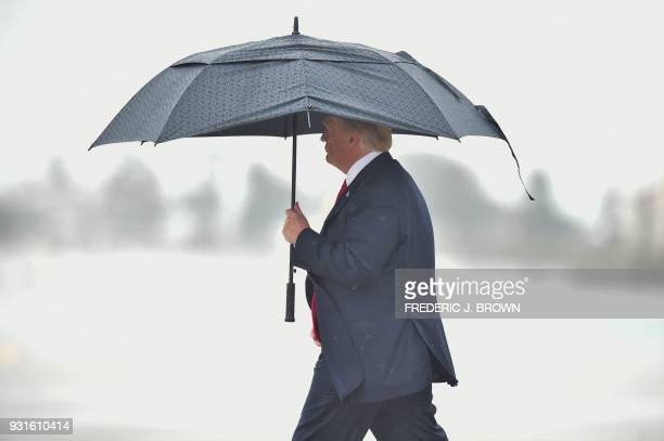 US President Donald Trump shelters from the rain under an umbrella as he arrives in Los Angeles California on March 13 2018