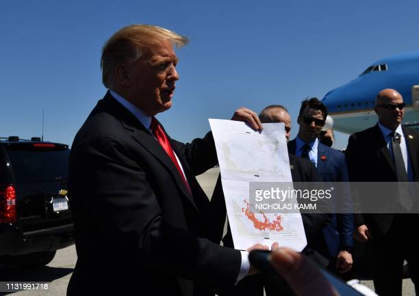 US President Donald Trump show a map which he said indicates the end of ISIS as he arrives at Palm Beach International Airport in Florida on March 22...