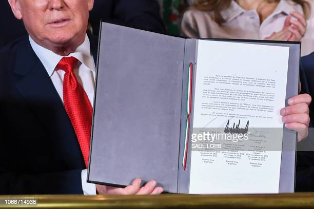 US President Donald Trump shows a document after signing a new free trade agreement with Mexico's President Enrique Pena Nieto and Canadian Prime...