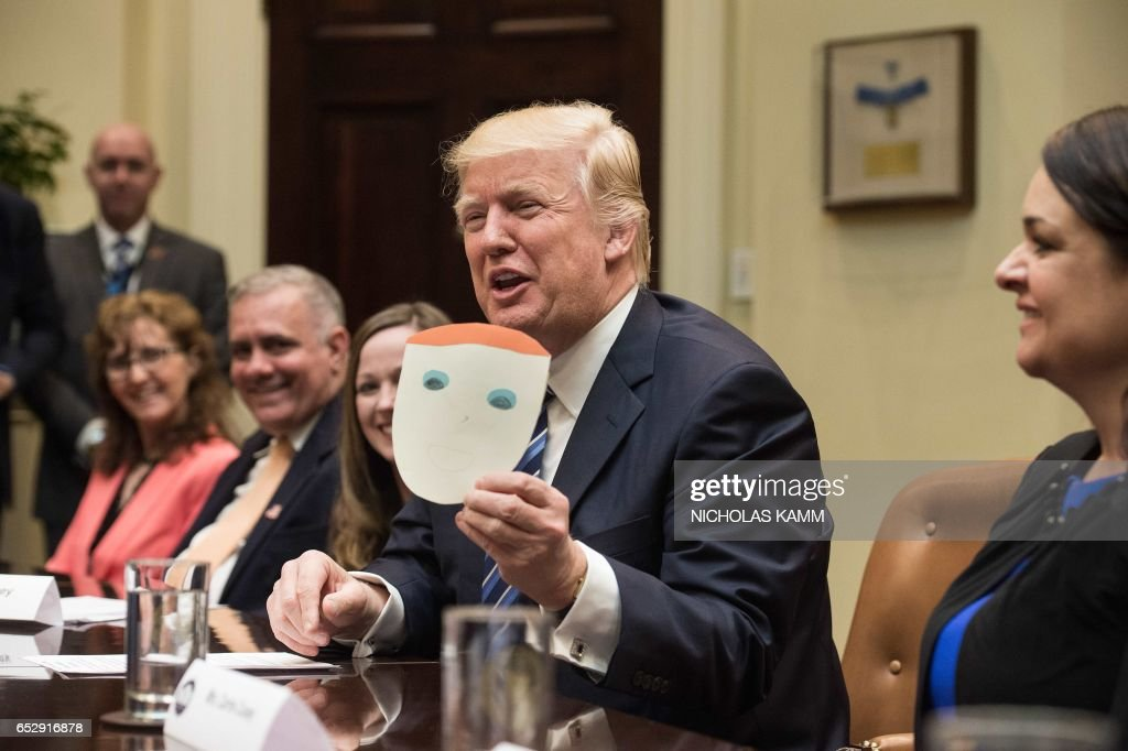 US President Donald Trump shows a picture of himself made by the son of participant Greg Brown during a meeting about healthcare in the Roosevelt Room at the White House in Washington, DC, on March 13, 2017. /