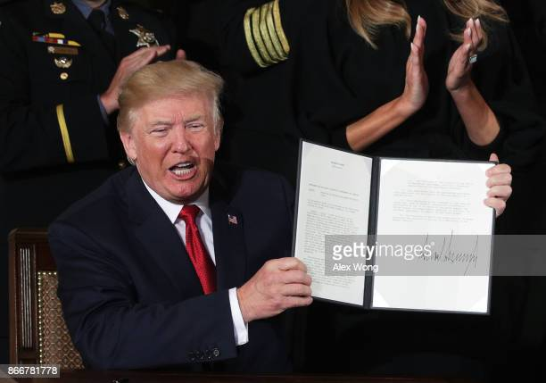 S President Donald Trump shows a presidential memorandum that he signed during an event highlighting the opioid crisis in the US October 26 2017 in...