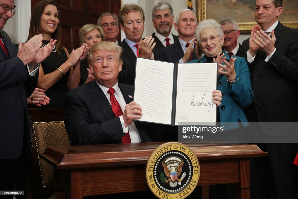 U.S. President Donald Trump shows an executive order after he signed it as Sen. Rand Paul (R-KY), Vice President Mike Pence, Rep. Virginia Foxx (R-NC) and Secretary of Labor Alexander Acosta look on during an event in the Roosevelt Room of the White House October 12, 2017 in Washington, DC. President Trump signed the executive order to loosen restrictions on Affordable Care Act 'to promote healthcare choice and competition.'