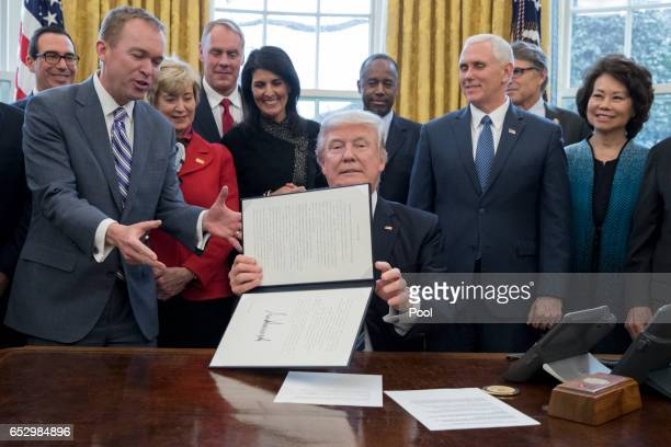 President Donald Trump shows an executive order entitled 'Comprehensive Plan for Reorganizing the Executive Branch' after signing it beside members...