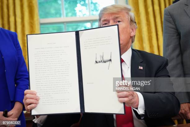 President Donald Trump shows an executive order on immigration which he just signed in the Oval Office of the White House on June 20, 2018 in...