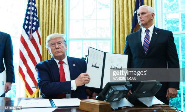 US President Donald Trump shows an executive order on sanctions on Iran's supreme leader in the Oval Office of the White House on June 24 2019