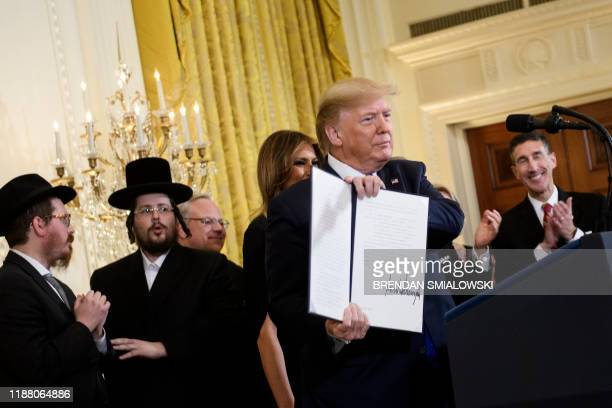 US President Donald Trump shows an executive order regarding antisemitism during a Hanukkah reception in the East Room of the White House December 11...