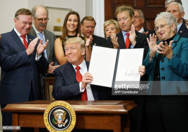 US President Donald Trump shows an executive order which he just signed on health insurance on October 12 2017 in the Roosevelt Room of the White...