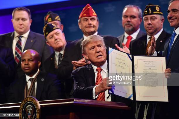 US President Donald Trump shows his signature after signing the Veterans Appeals Improvement and Modernization Act into law at the American Legion...