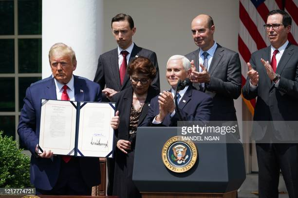 US President Donald Trump shows his signature on the Paycheck Protection Program Flexibility Act of 2020 as he holds a press conference on the...