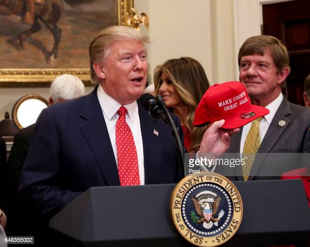 President Donald Trump shows off a hat that says 'Make Counties Great Again' before signing an Executive Order to begin the rollback of environmental...