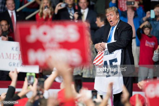 S President Donald Trump shows off a jersey during a campaign rally at the Bojangles Coliseum on October 26 2018 in Charlotte North Carolina...