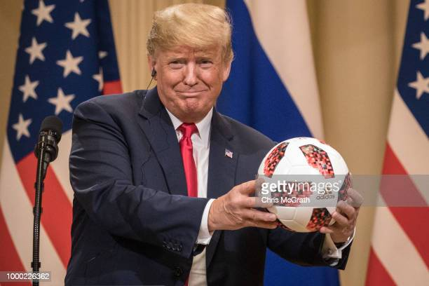 President Donald Trump shows off a World Cup football given to him by Russian President Vladimir Putin during a joint press conference after their...