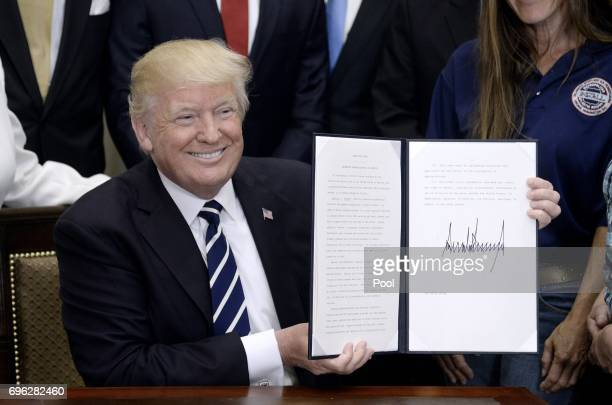 S President Donald Trump shows off his executive order that aims to expand apprenticeships to train people for millions of unfilled skilled jobs The...