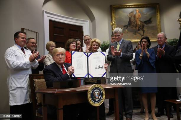 "S President Donald Trump shows off legislation he signed at a signing ceremony for the 'Know the Lowest Price"" Act and the ""Patient's Right to Know..."