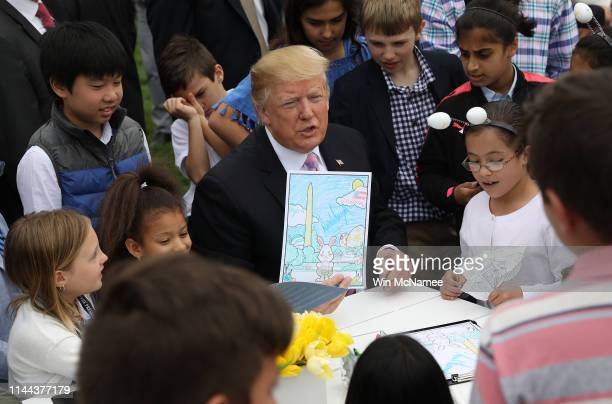 S President Donald Trump shows off pages from a coloring book while coloring with children during the 141st Easter Egg Roll on the South Lawn of the...