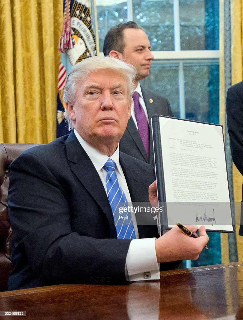 U.S. President Donald Trump shows the Executive Order titled 'Mexico City' which bans federal funding of abortions overseas after signing it in the Oval Office of the White House January 23, 2017 in Washington, DC. The other two Executive Orders concerned withdrawing the US from the Trans-Pacific Partnership (TPP) and a US Government hiring freeze for all departments but the military,.
