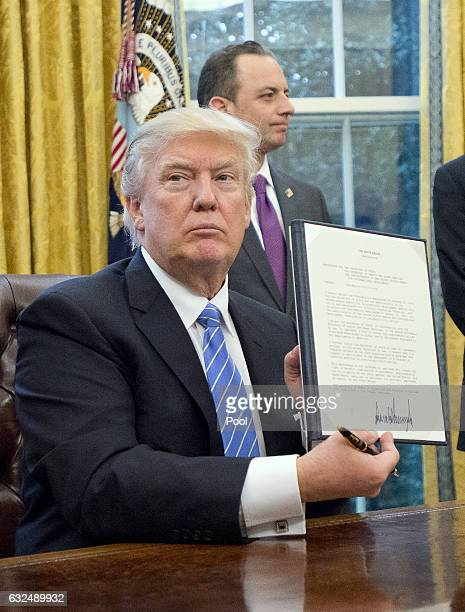 US President Donald Trump shows the Executive Order titled 'Mexico City' which bans federal funding of abortions overseas after signing it in the...