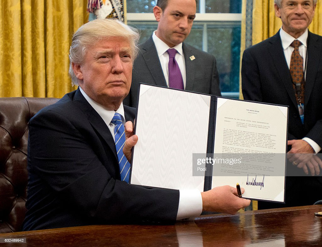 U.S. President Donald Trump shows the Executive Order withdrawing the US from the Trans-Pacific Partnership (TPP) after signing it in the Oval Office of the White House in Washington, DC on Monday, January 23, 2017. The other two Executive Orders concerned a US Government hiring freeze for all departments but the military, and 'Mexico City' which bans federal funding of abortions overseas.