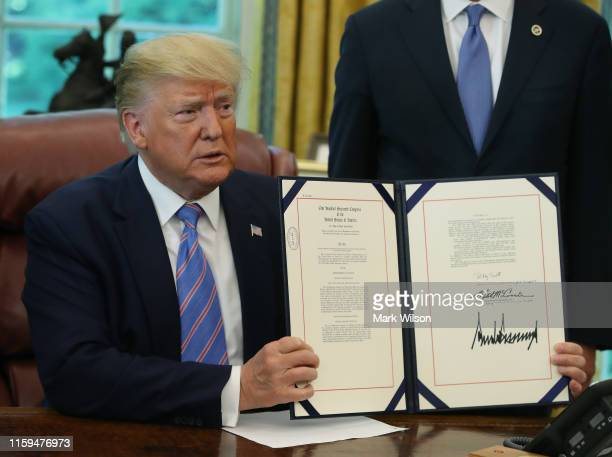 President Donald Trump shows the media a bill for border funding legislation he just signed in the Oval Office at the White House on July 1 2019 in...