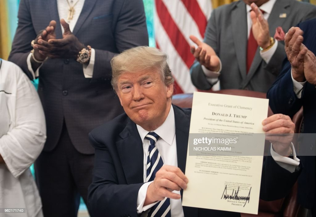 US President Donald Trump shows the posthumous pardon for former world champion boxer Jack Johnson after signing it in the Oval Office at the White House in Washington, DC, on May 24, 2018. - (Shown L-R)world champion heavyweight boxer Deontay Wilder, Trump, Keith Frankel, CEO of VitaQuest International, Stallone and former boxer Lennox Lewis.