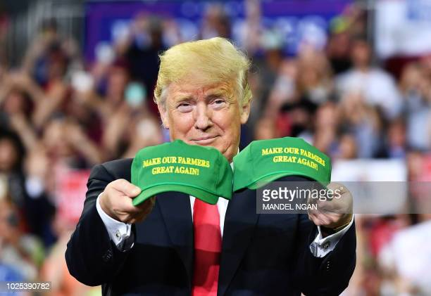 US President Donald Trump shows two caps as he arrives on stage for a campaign rally at Ford Center in Evansville Indiana on August 30 2018