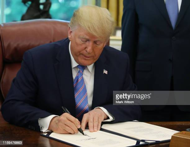 President Donald Trump signs a bill for border funding in the Oval Office at the White House on July 1 2019 in Washington DC