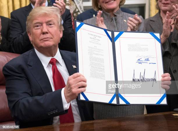 S President Donald Trump signs a bipartisan bill to stop the flow of opioids into the United States in the Oval Office of the White House on January...