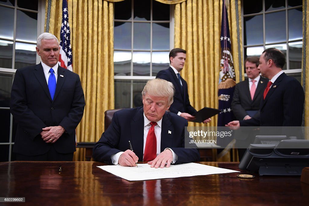 US President Donald Trump signs a confirmation for John Kelly as US Secretary of Homeland Security, as Vice President Mike Pence (L) and White House Chief of Staff Reince Priebus (R) look on, in the Oval Office of the White House in Washington, DC, January 20, 2017. / AFP / JIM