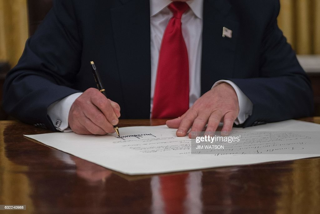 US President Donald Trump signs a conformation for General John Kelly as US Secretary of Homeland Security in the Oval Office of the White House in Washington, DC, January 20, 2017. / AFP / JIM